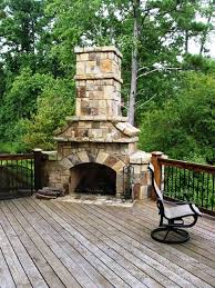 stone stacked massive corner fireplace on wooden deck outdoor