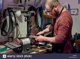 man sharpening kitchen knife on belt sander usa stock photo