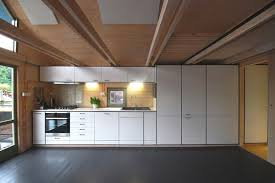 compact one wall kitchen with white cabinets and wooden backsplash