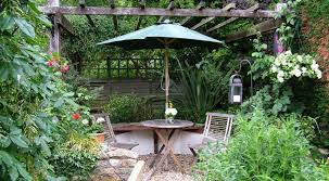 small tuscan garden design with wooden furniture and pergola with