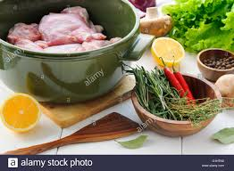 White Wooden Table Surface Raw Rabbit Meat With Vegetables And Herbs In Round Ceramic Pot On