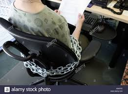 Secretary Desk Chair by Female Office Worker Is Chained To Office Chair And Desk Stock