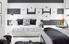 black white bedroom blue and white cloud wallpaper behind a bed
