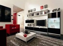 lcd tv on black glossy tv cabinet connected by square white sofa