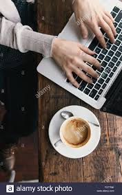 overhead view of woman u0027s hands typing on laptop at coffee shop