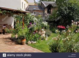 backyard garden with perennial beds lawn and terrace with potted