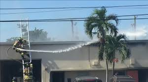 car junkyard broward county firefighter falls from ladder while battling pompano beach fire