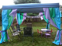 backyard pop up tent decorated with strips of plastic tablecloths