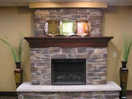 grey brick fireplace with dark brown wooden mantel shelf and grey