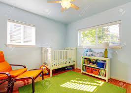 baby nursery room design with green rug blue walls and orange