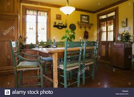 cottage style dining chairs wooden dining table with green high back chairs in the kitchen