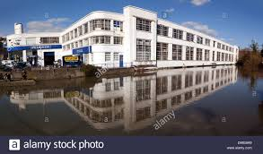 an art deco 1930 u0027s style building reflected in an old millpond on