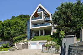 a house on a slope connects to its surroundings through a glass