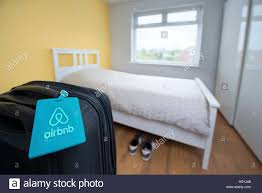 rent a bedroom an airbnb branded luggage tag tied to a suitcase in a bedroom stock