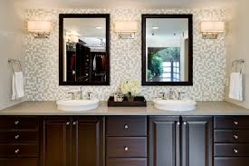 bathroom tile wall with double wall mirror and round sink plus