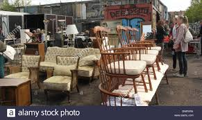 household furniture people standing looking open air market stall selling household