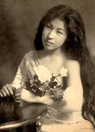 portrait of a geisha or geiko with her hair down holding flowers
