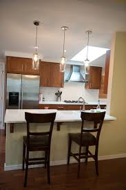 glass pendant lighting above white quartz counter top and ikea