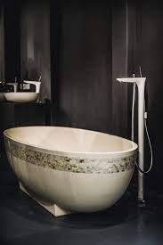 cream standing tub with glass mosaic ornament laid on black tiled