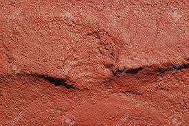 an abstract terracotta color painted wall texture background stock