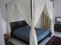 low platform bed and sheer canopy curtains placed inside