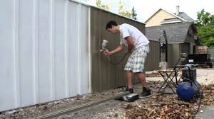 painting a fence with an air spray paint gun solid oil stain
