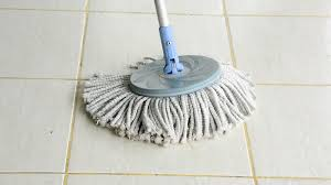a moving cloth mop is used to clean a white tile floor cloth mop