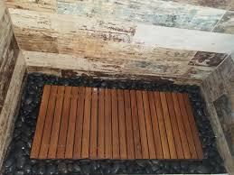teak wood shower floor surrounded by river rock walls tiles in