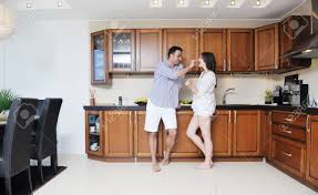 happy young couple have fun in modern wooden kitchen indoor