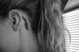 black ink feather tattoo on left behind the ear by gabriela