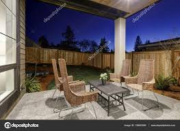 backyard covered patio design with high back wicker chairs u2014 stock