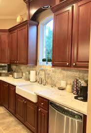 what backsplash looks with cherry cabinets tumbled travertine backsplash with maestro quartz kitchen