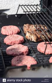 Outdoor Barbecue Hamburgers And Steaks Being Grilled On An Outdoor Barbecue Stock