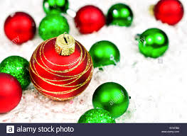 and green ornaments on snow background stock photo