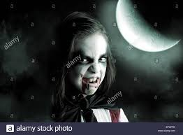 with face paint and halloween vampire costume in a dark stock