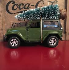 jeep girls sayings green jeep wrangler carrying christmas tree ornament by