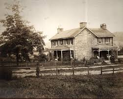 old photo of stone house with side porch underground railroad