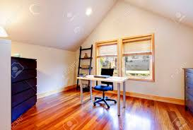 study room with hardwood floor dark blue cabinets and vaulted