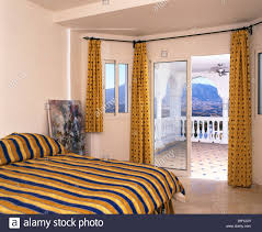Spanish Bedroom Furniture by Yellow Striped Bed Cover On Bed In Modern Spanish Bedroom With