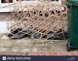 broken garden trellis panels dumped in front a house stock photo