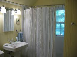 bathroom silver curved shower curtain rod on yellow wall plus