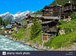 listed townscape with swiss chalet houses in front of valais alps