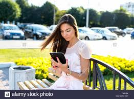 beautiful holding tablet bright sunny day on a bench