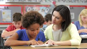 Picture Of Student Sitting At Desk Teacher Sitting At Desk Next To Female Student As They Read