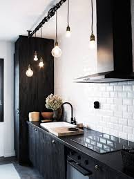 kitchen 20 black kitchens that will change your mind about using kitchen black modern faucet bulb pendant lights brick wall electric stove faucets wood cutting board chimney
