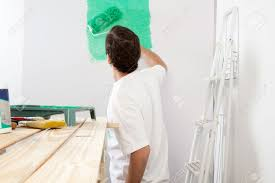 man painting the wall with roller and brush stepladder in man painting the wall with roller and brush stepladder in background stock photo 10033185
