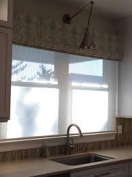 ikat fabric valance over translucent woven shade on kitchen sink