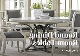 glass table black legs plain white wall plain white vas rattan chairs with plaid black and