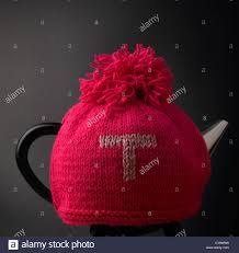 contemporary teapot and traditional knitted woollen tea cosy