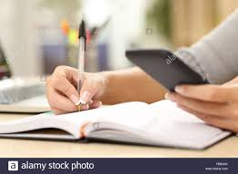 Office Desk Close Up Woman Hand Writing In Agenda Consulting A Mobile Phone On A Desk